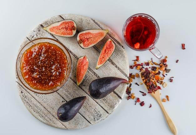 Figues avec confiture, tasse de thé, herbes séchées à plat sur une planche en bois et blanc