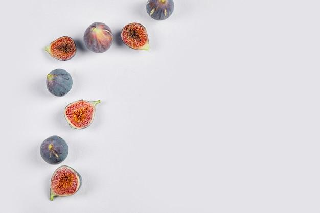 Figues entières et demi violettes sur l'espace blanc.