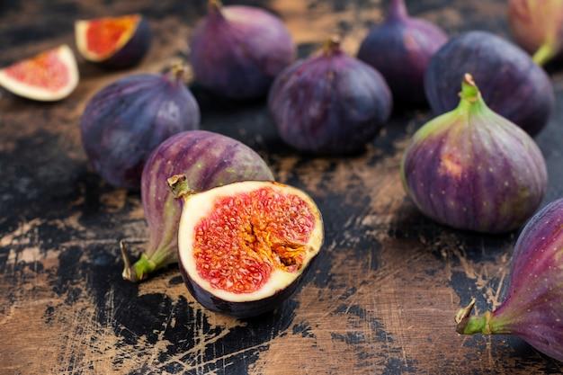 Figues fraîches entières et coupées sur table en bois