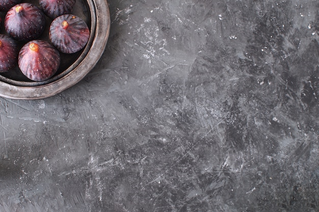Figues fraîches sur plaque de céramique noire fond de béton noir