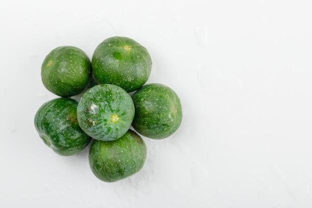 Figues fraîches à plat sur un mur blanc