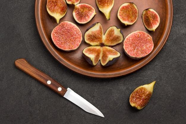 Figues hachées dans une assiette en céramique. couteau et quart de figues sur table. fond noir. mise à plat