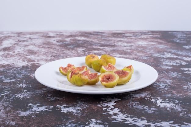 Figues jaunes avec graines rouges dans une assiette blanche isolée sur bleu.