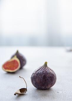 Des figues juteuses mûres se trouvent sur une table blanche près de la fenêtre. lumière du matin. fermer et copier l'espace