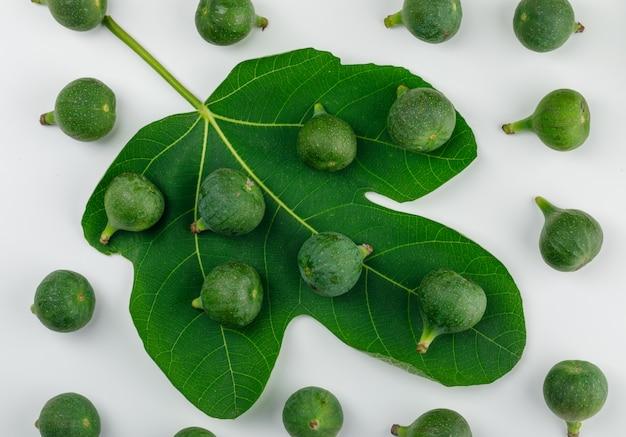 Figues mûres avec des feuilles sur un mur blanc, à plat.