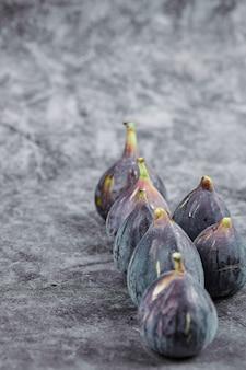 Figues mûres violettes sur marbre.