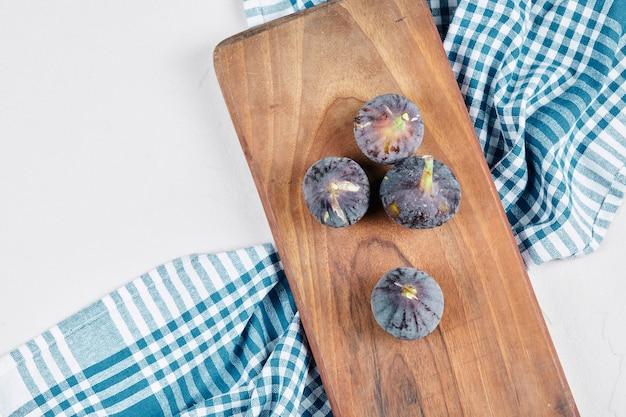 Figues sur planche de bois avec une nappe bleue.