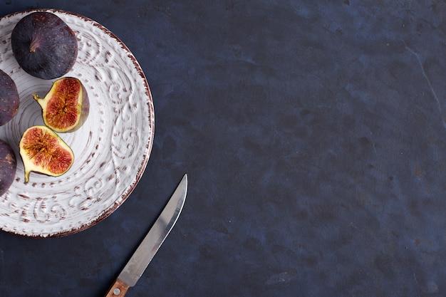 Figues sur plaque noire sur fond de table en bois