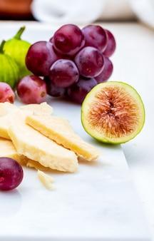 Figues, raisins rouges et fromage de brebis (type manchego). sur marbre blanc et bois.