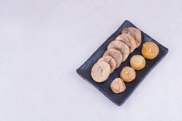 Figues séchées et cerises sur un plateau en céramique.
