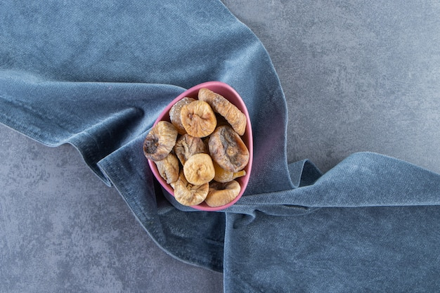 Figues séchées dans un bol sur un morceau de tissu, sur fond de marbre.