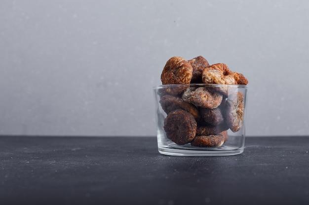 Figues séchées dans une tasse en verre sur fond gris.
