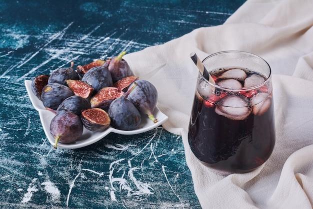 Figues Avec Une Tasse De Boisson Sur Bleu. Photo gratuit
