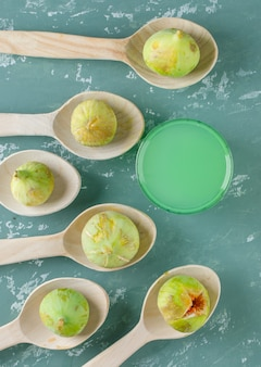 Figues vertes avec boisson dans des cuillères en bois sur mur de plâtre, vue du dessus.
