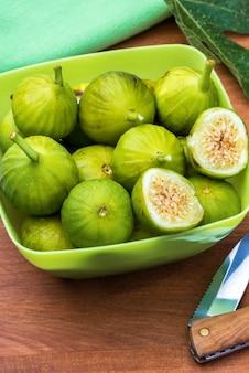 Figues vertes fraîches et mûres avec une surface en bois de feuille de figuierfigues vertes fraîches et mûres entières et coupées avec une feuille de figuier et un couteau surface en bois