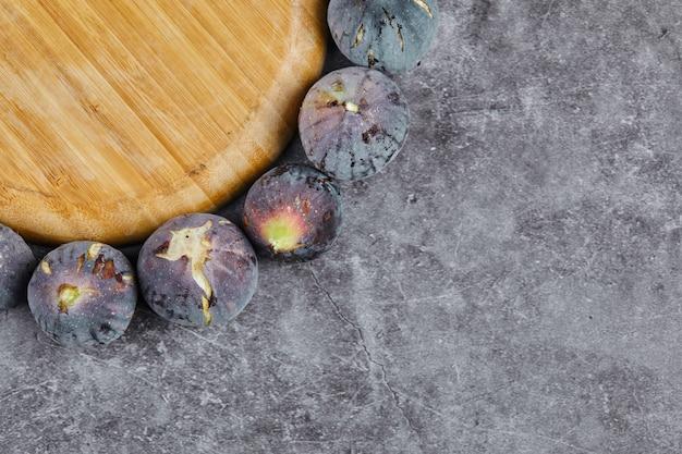 Figues violettes autour d'une assiette en bois sur marbre.