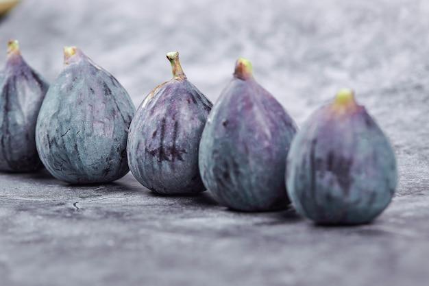 Figues violettes mûres sur une table en marbre.