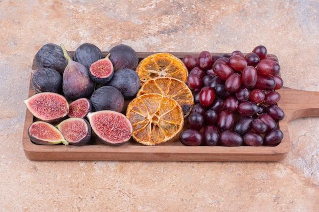 Figues violettes avec des tranches d'orange sèches et des baies de cornouiller sur une planche de bois