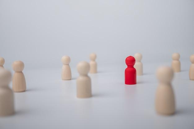 Une figure en bois debout avec une équipe pour influencer