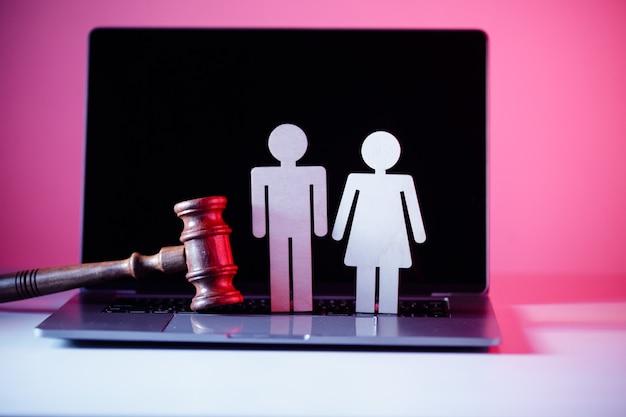 Figure en bois en forme de personnes et marteau sur la table concept de droit de la famille