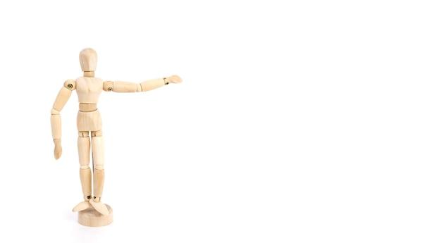 La figure en bois d'un homme montre avec sa main la direction sur un fond blanc, simule un endroit pour insérer du texte ou des objets.