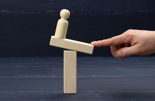 Une figure en bois d'un homme se dresse sur une balançoire, son doigt garde l'équilibre