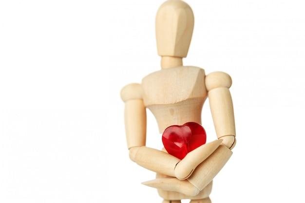 La figure en bois d'un homme tient dans ses mains un coeur rouge sur une surface blanche, donne le coeur