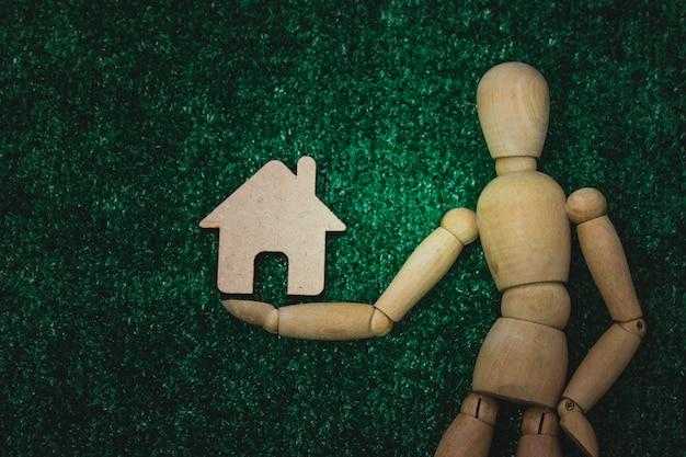Figure en bois avec maison en bois dans le concept d'entreprise.