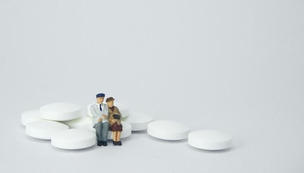 Figure de couple de personnes âgées assis sur un tas de pilules blanches.