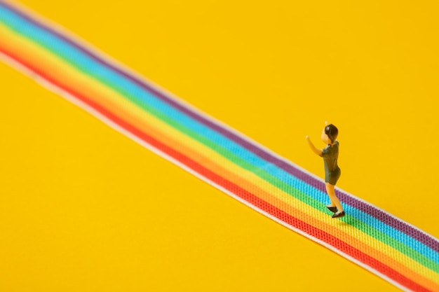 La figure du petit garçon se tient sur la bande lgbt arc-en-ciel sur fond jaune