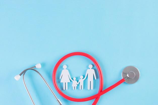 Figure de famille enveloppée de stéthoscope sur fond bleu clair. assurance ou concept covid-19.