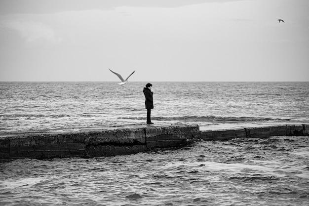 Figure féminine solitaire sur le brise-lames du bord de mer, photo bw