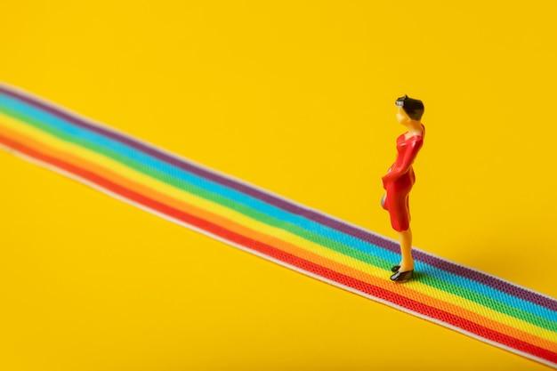 Figure de femme adulte debout sur une bande lgbt arc-en-ciel sur fond jaune