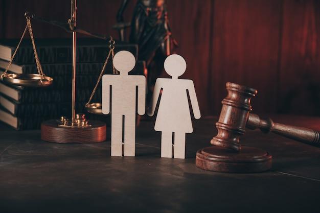 Figure en forme de personnes et marteau sur table en bois.