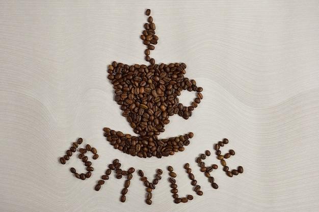 Une figure en forme de tasse de café avec une soucoupe est disposée à partir de grains de café