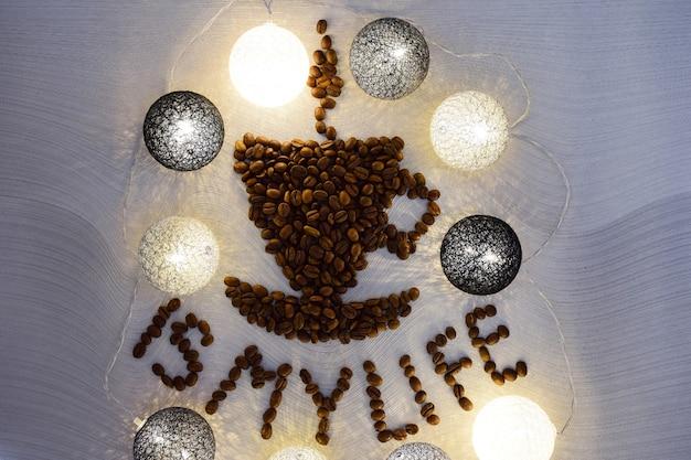 Une figure en forme de tasse de café avec une soucoupe est faite de grains de café