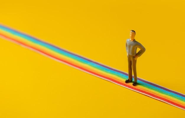 Figure d'homme adulte debout sur une bande lgbt arc-en-ciel sur fond jaune