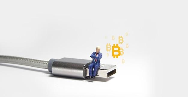 Figure d'homme d'affaires assis sur un câble usb de type c.