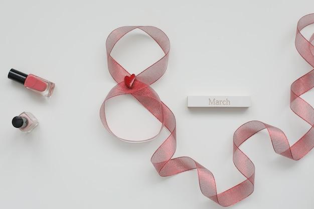 Figure huit du ruban rouge et mot mars sur fond blanc.
