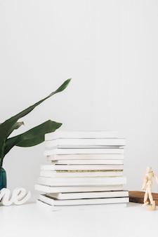 Figure humaine et plante près de livres