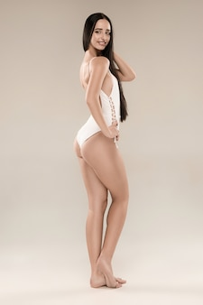 La figure de jeune fille en maillot de bain sur fond de studio