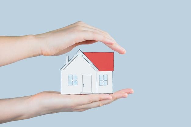 La figure d'une maison entre des mains humaines.