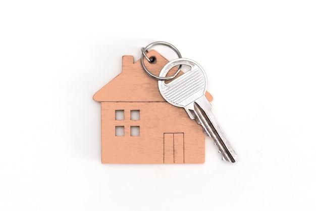Figure d'une mini maison de couleur beige avec des clés sur un fond blanc isolé.