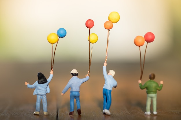 Figure miniature d'enfants avec des ballons colorés debout, marcher et jouer ensemble sur une table en bois.