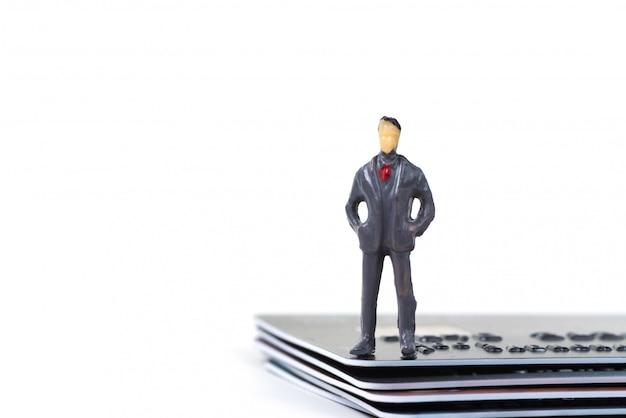 Figure miniature homme d'affaires permanent avec pile de carte de crédit