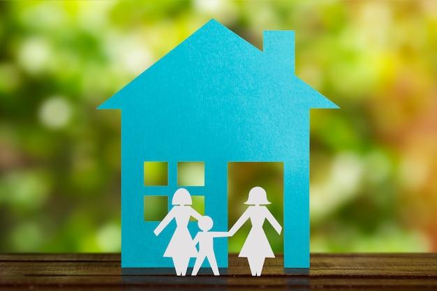 Figure en papier d'un couple gay se tenant la main avec un enfant en famille d'accueil. maison bleue et fond dénommé. diversité, concept de minorités.