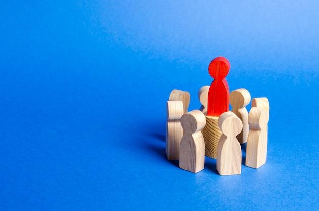 La figure rouge du chef au centre du cercle de personnes.