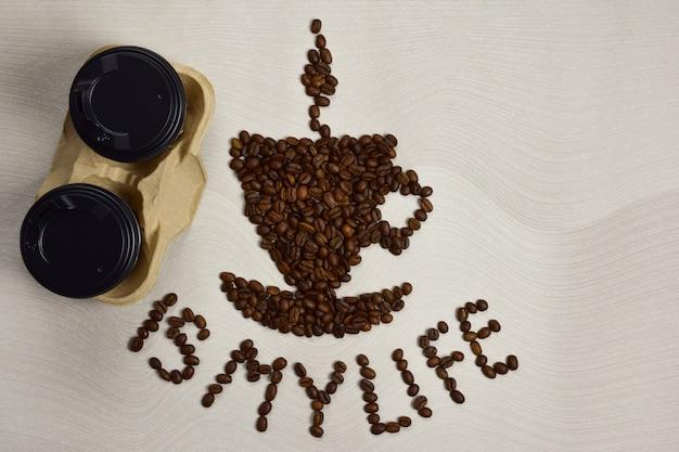 Une figure sous la forme d'une tasse de café avec une soucoupe est faite de grains de café