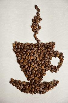 Une figure sous la forme d'une tasse avec une soucoupe au-dessus de la vapeur est disposée à partir de grains de café