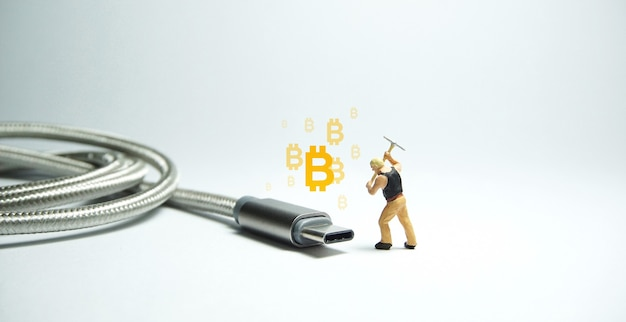 Figure de travailleur technicien debout devant un câble usb usb de type c. concept d'exploitation minière de bitcoin.